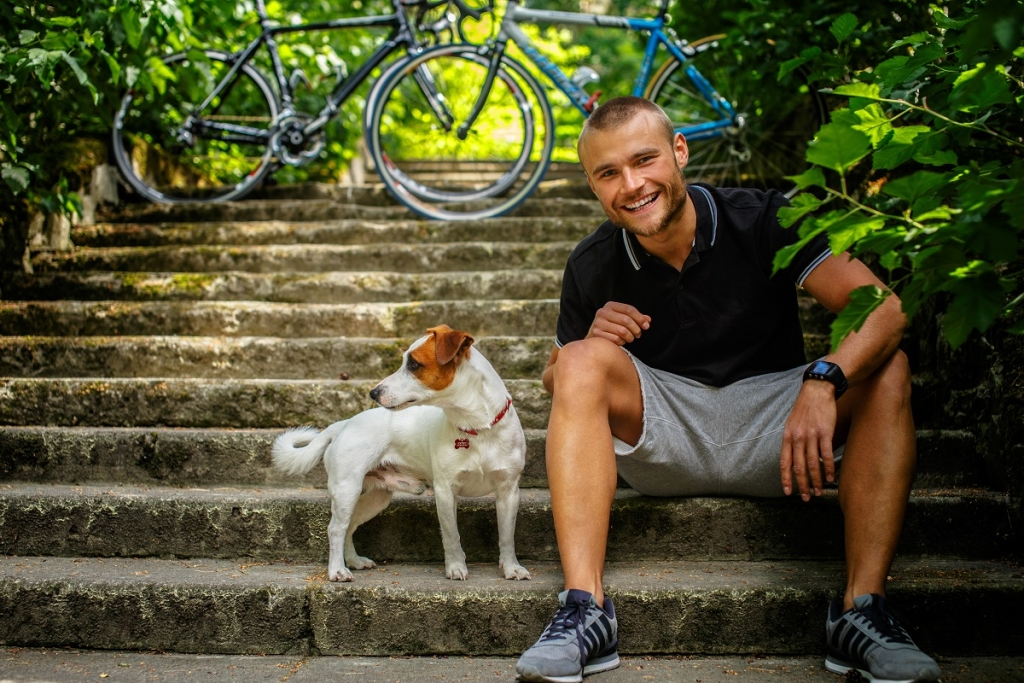 Man with dog sitting on stairs. Bicycles on background.