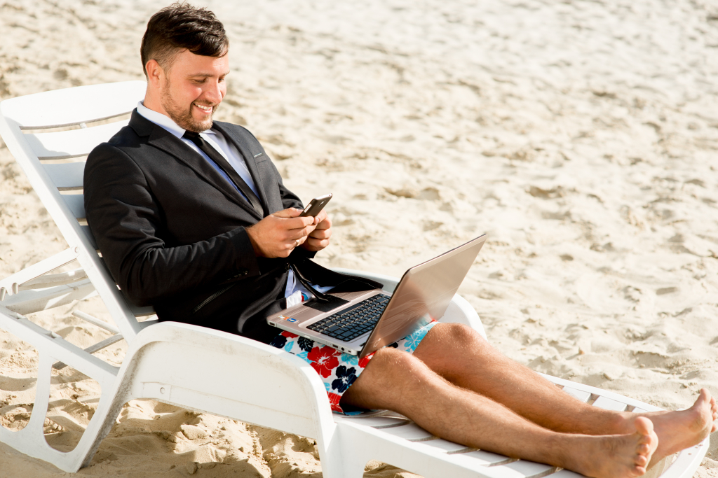 Businessman dressed in suit and shorts working with laptop on the sunbed at the beach