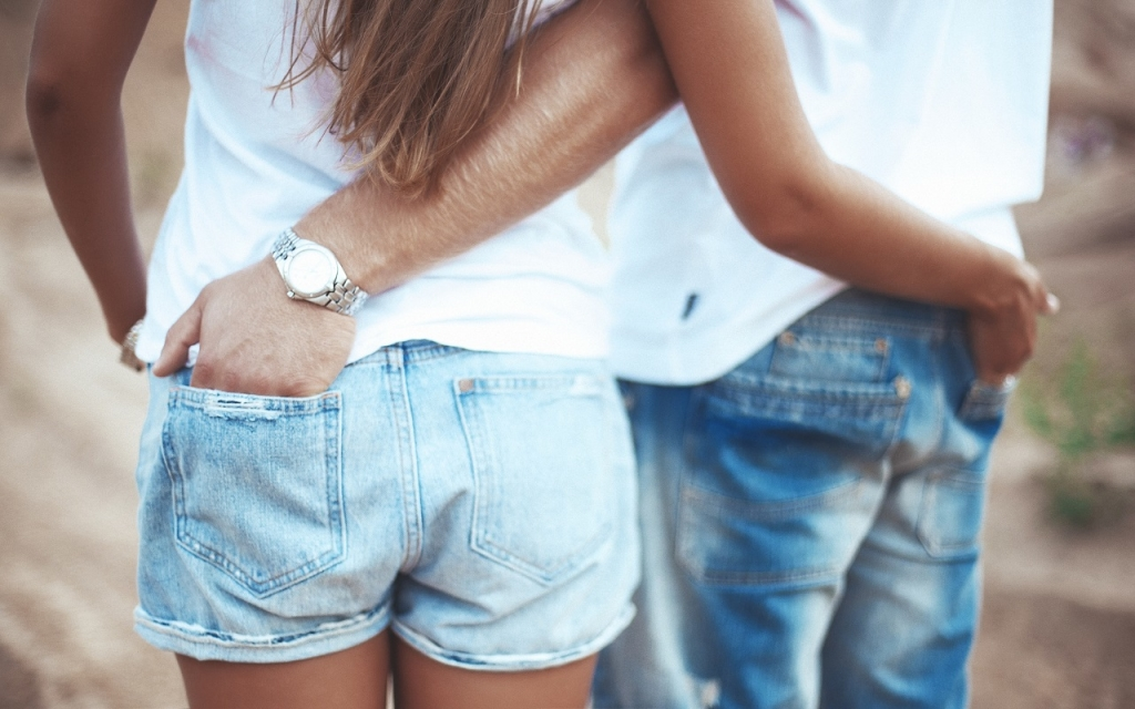 Couple holding hands in each other pocket in love