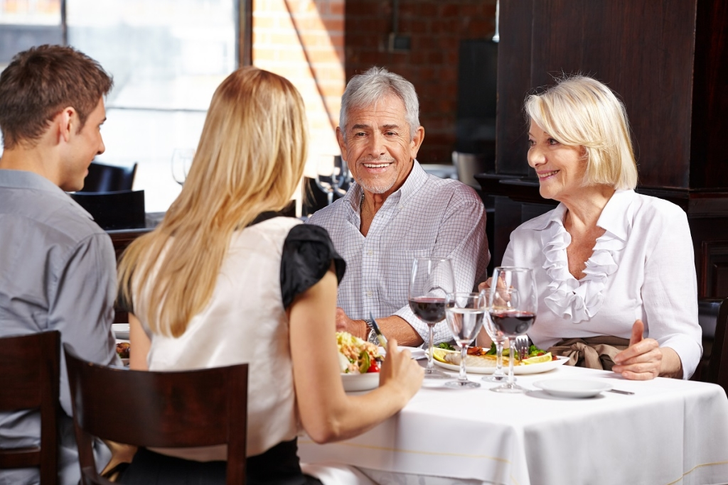 Couple with family eating out in a restaurant and talking