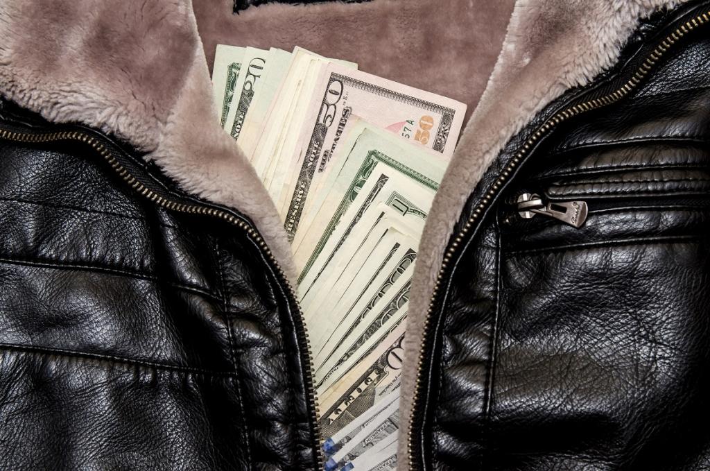 dollar bills in the pocket of leather black jacket