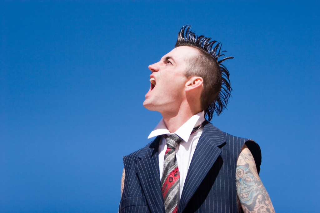 Man with mohawk style haircut and alternative fashion outfit