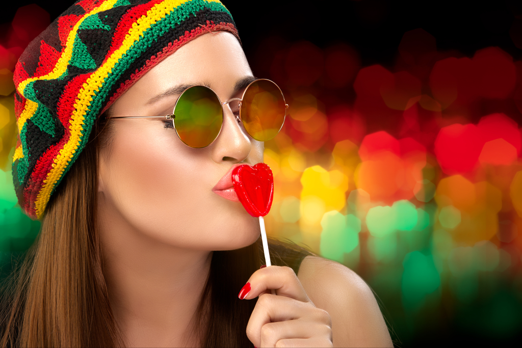 Stylish Party Girl in Rastafarian Hat and Trendy Round Sunglasses Kissing a Heart Shaped Lollipop. Close up portrait on an Colorful Abstract Background with Copy Space.