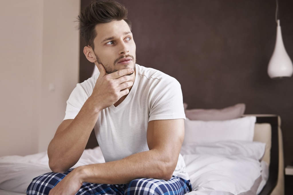Pensive man sitting at the edge of the bed