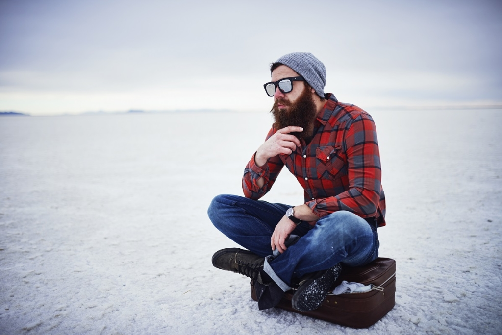beard lumbersexual hipster sitting on suitcase in deep thought