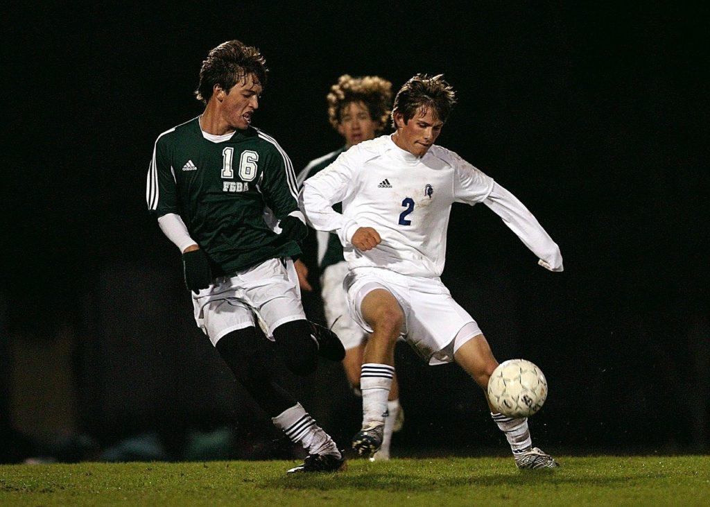 Piłkarze grają w piłkę podczas meczu piłkarskiego
