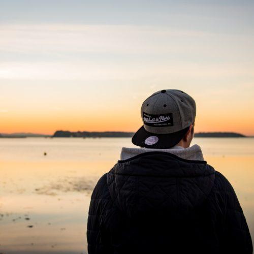 mężczyzna w kurtce nad jeziorem