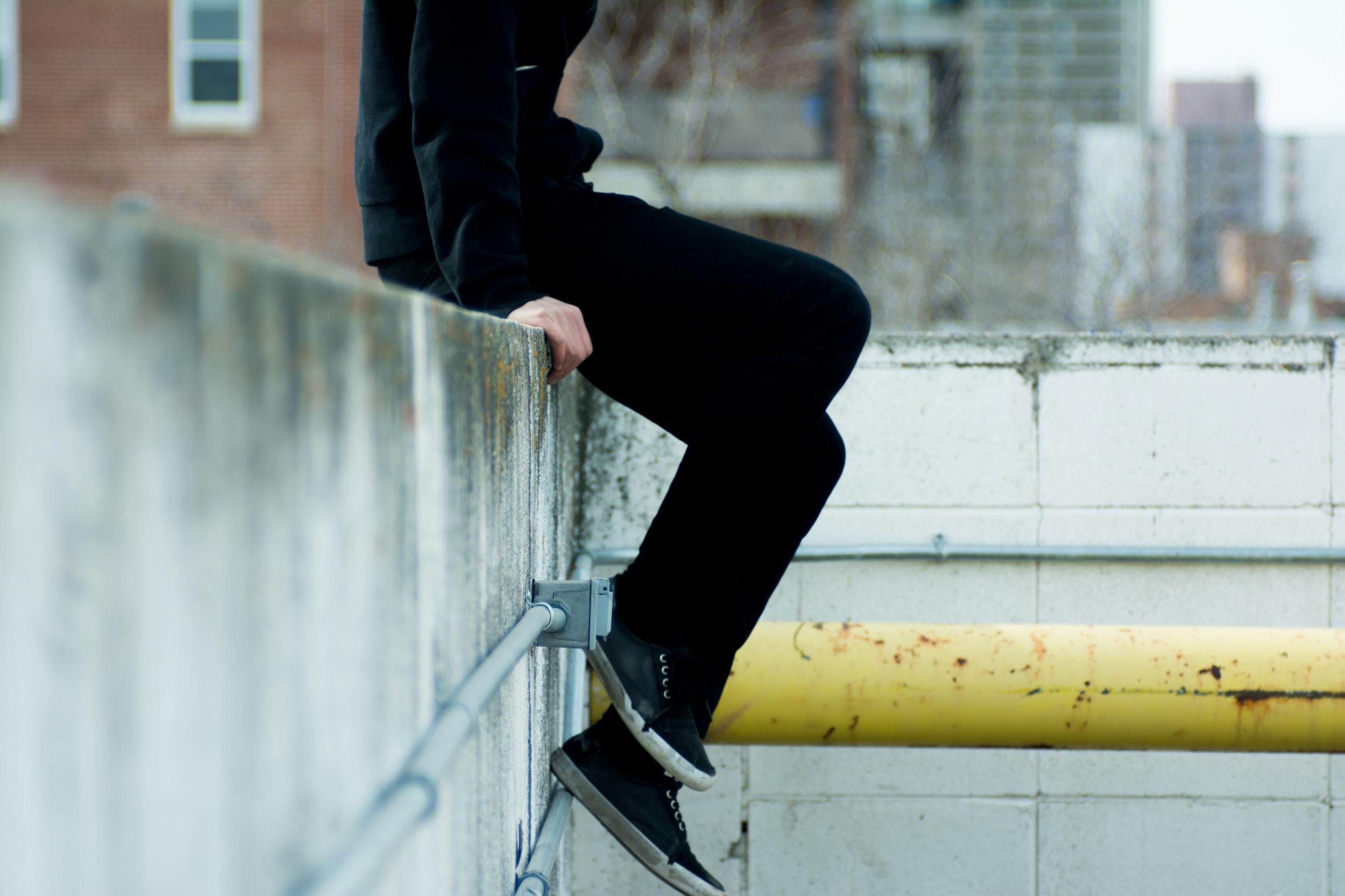 osoba siedząca na murku ubrana na czarno